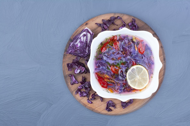 Purple cabbage soup with chili peppers on a wooden board