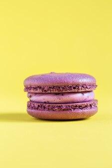 Фиолетовый торт макарон или миндальное печенье на желтой стене. разноцветное миндальное печенье. французское миндальное печенье