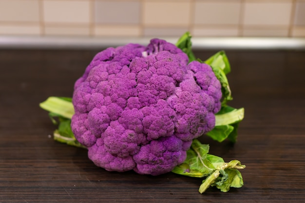Purple cauliflower on a wooden table in the kitchen