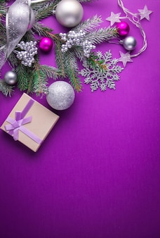 Purple christmas background with a gift, fir tree, toys and bows