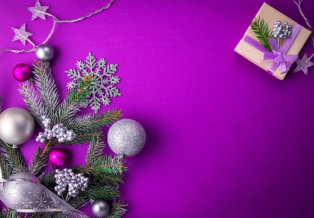 Purple christmas background with a gift, fir tree, toys ...