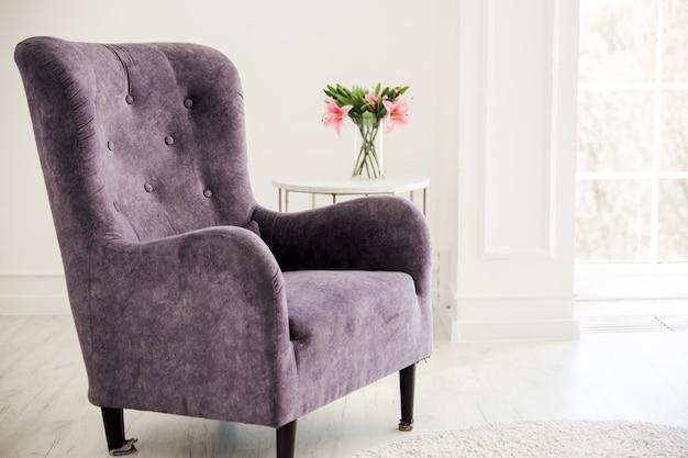 Purple corduroy armchair stands opposite the window.