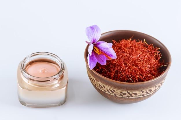 紫色のクロッカスの花、セラミックボウルにサフランのおしべ、白い背景の化粧クリーム。