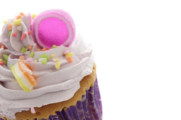 白で隔離される紫色のカップケーキ