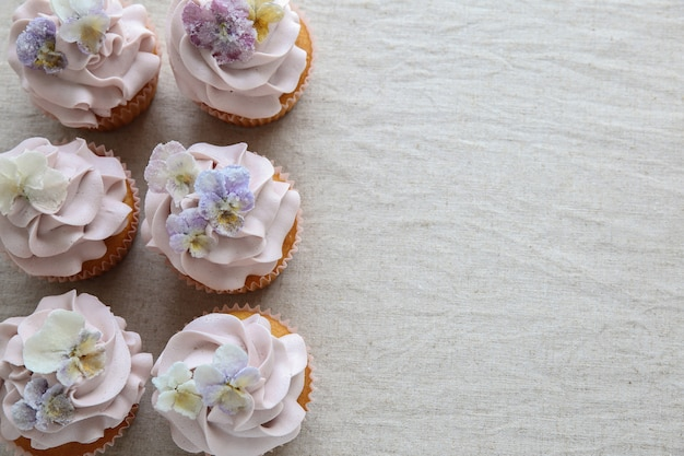 Purple cupcakes with sugared edible flowers copy space
