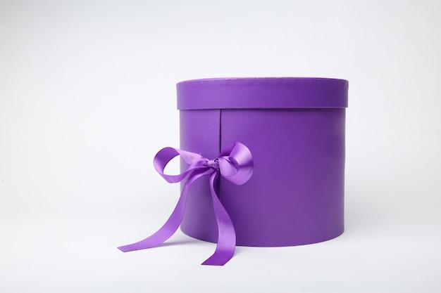 Фиолетовая цилиндрическая подарочная коробка, изолированная на белом