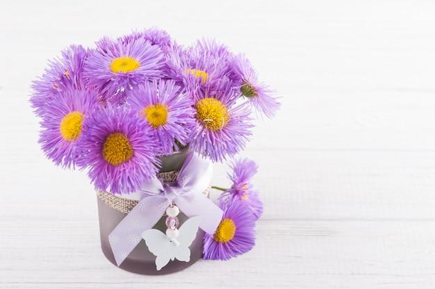 Purple daisies on white table