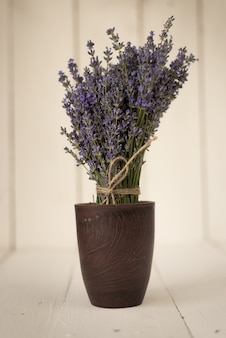 Purple delicate bouquet of lavender flowers in a vintage wooden glass with the smell of french provence.