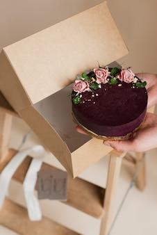 손에 보라색 디저트. 꽃 장식 케이크. 선물 상자에 케이크. 밝은 배경에 디저트