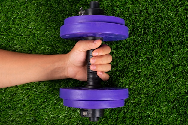 Purple dumbbell in hand on green grass