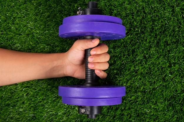 緑の芝生に手で紫のダンベル