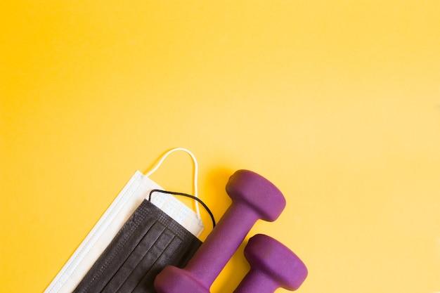 Фиолетовые гантели и медицинские защитные маски разных цветов на желтой поверхности