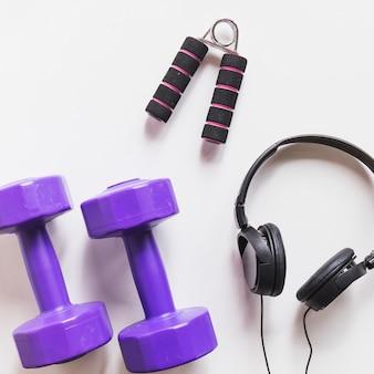 Фиолетовые гантели; наушники и ручка на белом фоне