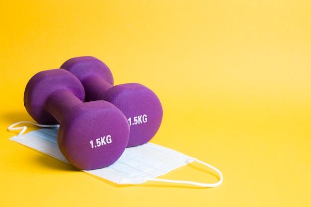 黄色の表面の医療用保護マスクに紫色のダンベル