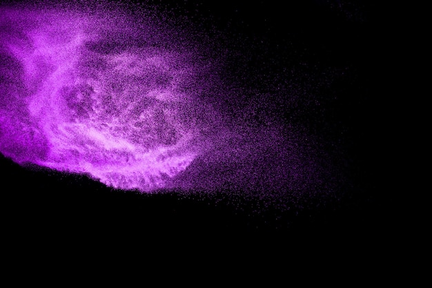 Purple dust particles explosion on black background. color powder dust splashing.