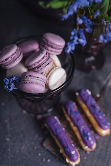 Purple eclairs on spatula with macaroons in glass bowl near the vase