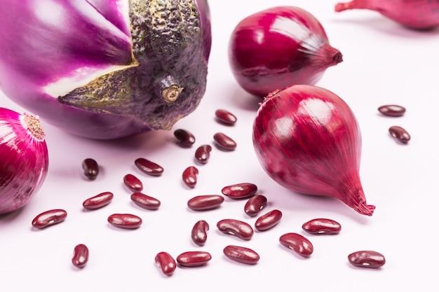 テーブルの上の紫色のナス、青玉ねぎと豆。閉じる。上面図。白色の背景