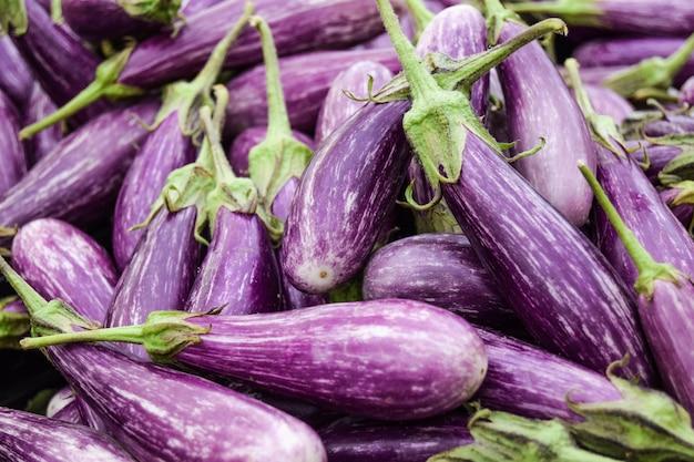 Фиолетовая предпосылка баклажанов в органическом рынке. овощи из местного сельского хозяйства.