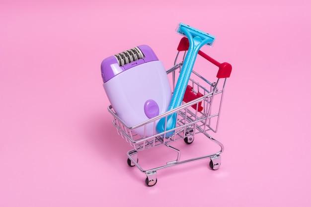 Фиолетовый эпилятор и синяя бритва в тележке супермаркета