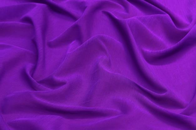 Фиолетовый фон и текстура ткани, мятый фиолетовый атлас для абстракции и дизайна