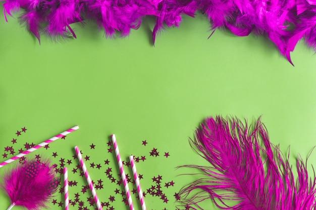 Piuma viola con coriandoli su un tavolo verde