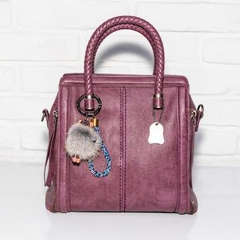 白い表面に紫色の女性のバッグ
