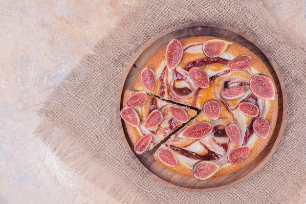 과일 나무 플래터에 보라색 무화과 파이.