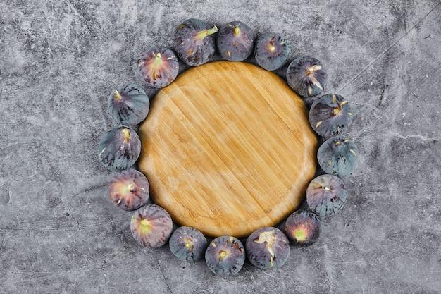 Fichi viola intorno a un piatto di legno su marmo.