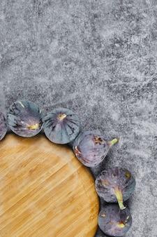 Purple figs around a wooden plate on marble.