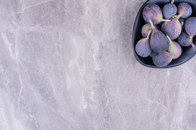 Purple figs in a black bowl on the marble