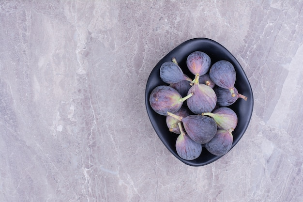 Purple figs in a black ceramic bowl.