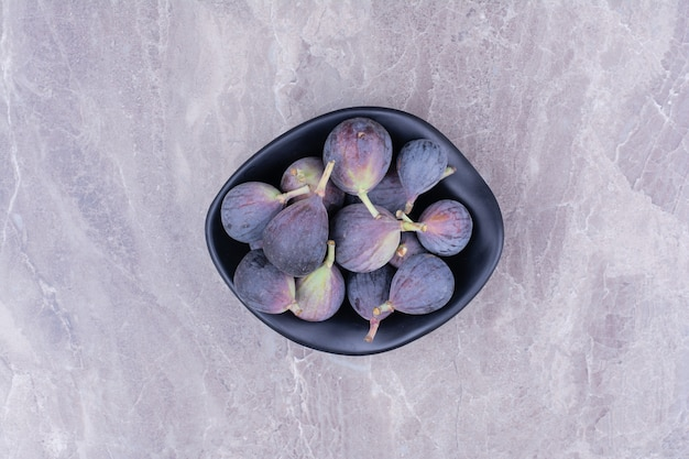 Purple figs in a ceramic black bowl, top view.