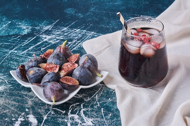 Purple figs and a cup of drink on blue.