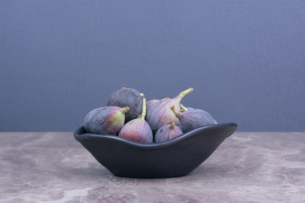 Purple figs isolated in a black ceramic saucer