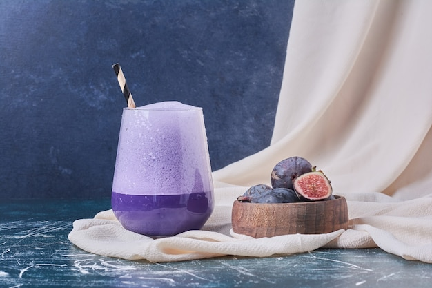 Purple figs with a cup of drink on blue.