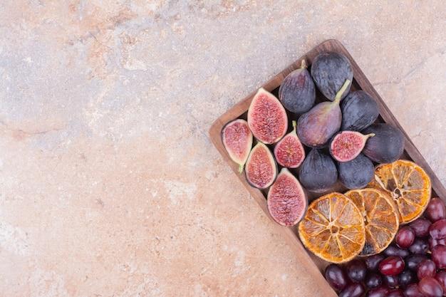 Fichi viola con fette d'arancia secche e bacche di corniolo su una tavola di legno