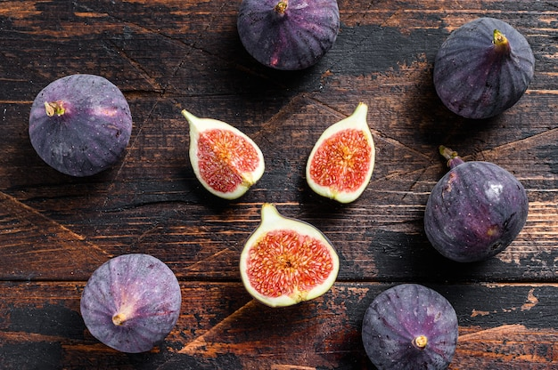 Purple figs on a wooden table. dark wooden background. top view.