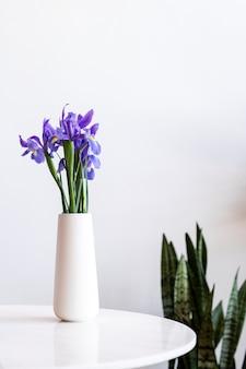 테이블에 흰색 꽃병에 보라색 꽃