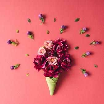 ピンクの壁に紫色の花と緑のアイスクリームコーン。フラットレイ。