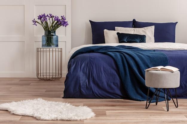 킹 사이즈 침대 옆의 세련된 침대 옆 탁자에 있는 파란색 유리 꽃병에 보라색 꽃