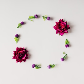Purple flowers and roses arranged in circle. flat lay.