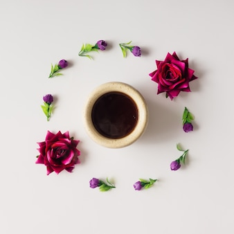 Purple flowers and roses arranged in circle with coffe cup. flat lay.