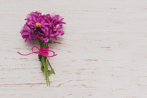 Purple flowers tied on white wooden surface