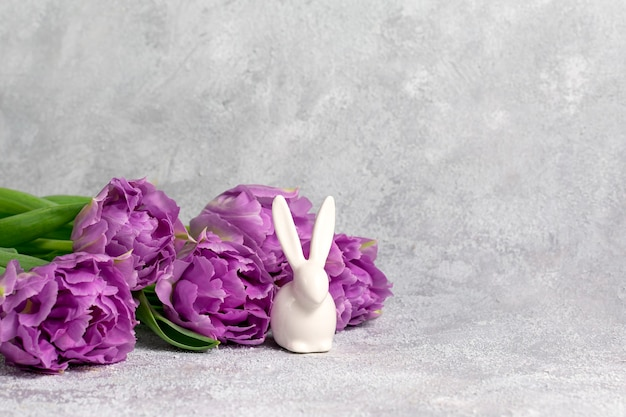 Purple flowers and white bunny figure on white marble background.