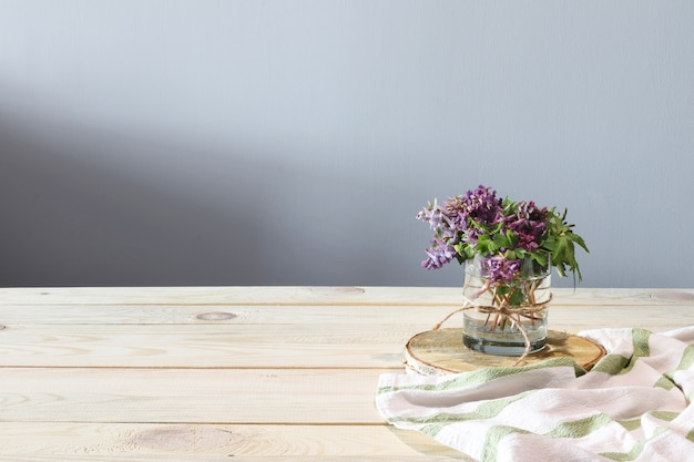 Purple flowers and white towel on wooden desk
