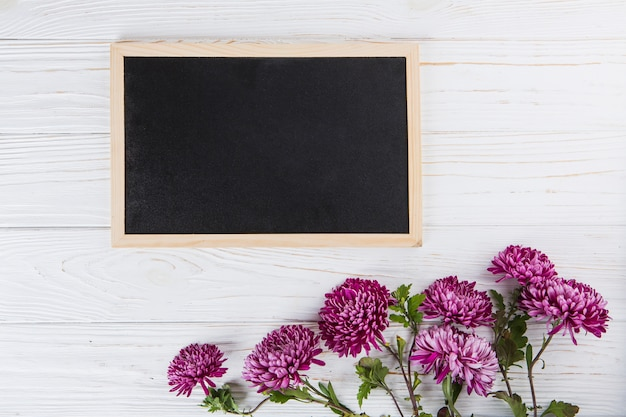 Purple flowers with blank chalkboard on white table