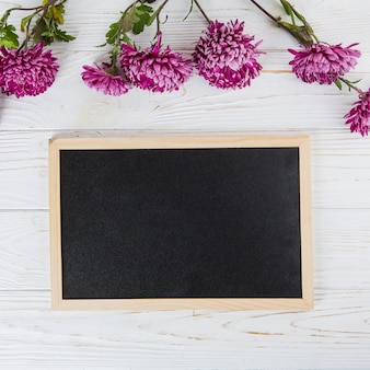 Purple flowers with blank chalkboard on wooden table