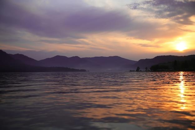 Фиолетовый туман над озером в сумерках в горах, устанавливающий пейзаж