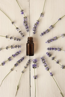 Purple fragrant flowers are arranged around the jar of lavender oil. elite perfumery. flat lay