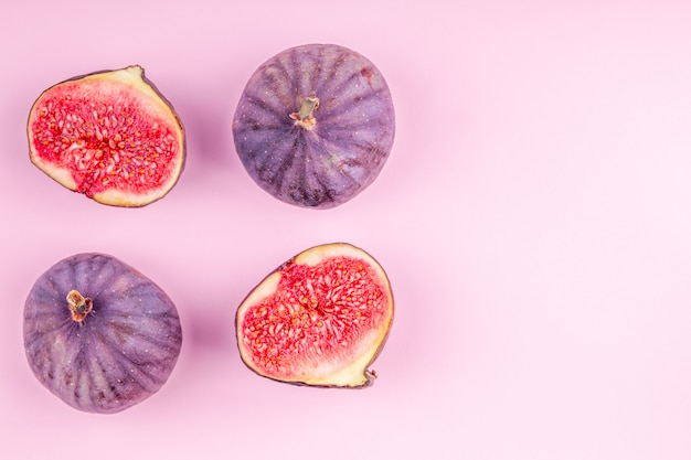 Purple fresh whole and sliced figs on pink paper background with copy space